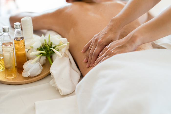 Lady having a massage in a spa environment, with essential oils.