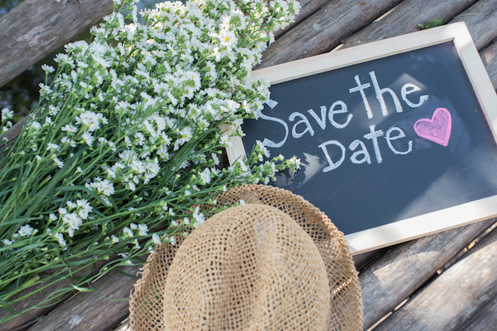 Save the date board with flowers and straw hat laid on bench.
